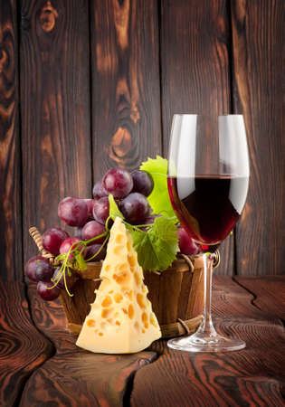 Wine glass and cheese in a basket on a wooden background photo