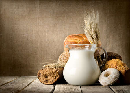 milk jugs: Milk and bread on canvas Stock Photo
