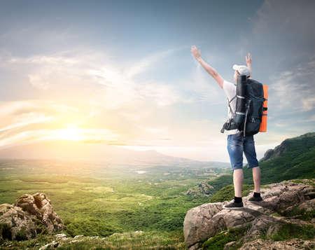 путешествие: Туристический с рюкзаком насладиться видом на долину с вершины горы Фото со стока