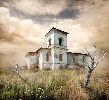 aAbandoned church near the cemetery in a field photo