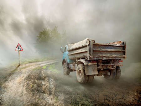 Dirty truck on a country road and cloudy sky photo