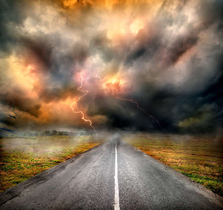 middle of the road: Storm clouds and lightning over highway in the field