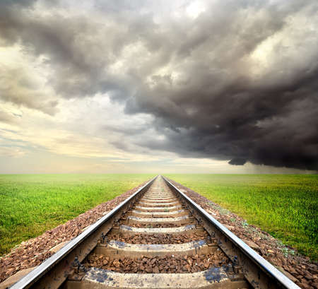 railway track: Railway in the field and storm clouds