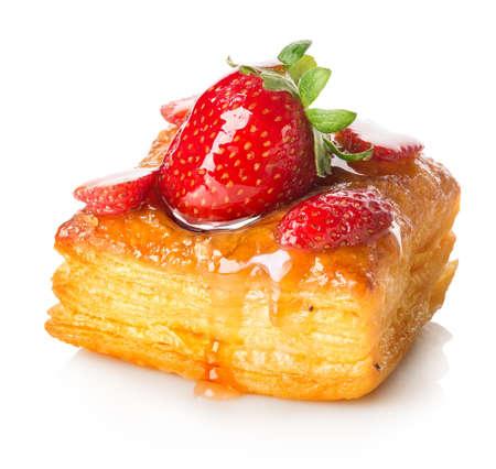 白で隔離されるいちごパイ生地のケーキ