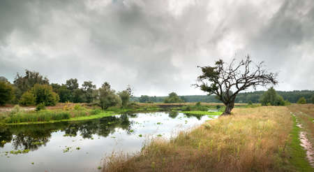 Cloudy sky over the river in autumn photo