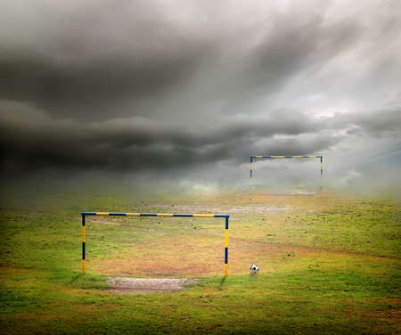 open gate: Football field, football goal, deflated ball and cloudy sky Stock Photo