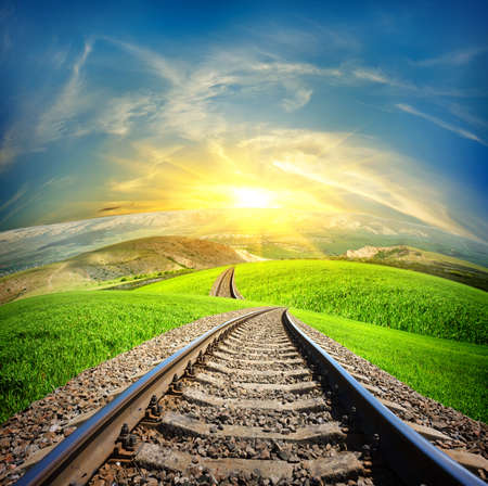 Railway in mountain fields in the sunlight Banco de Imagens