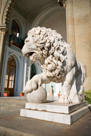 Sculpture of lion with a ball on a background of palace Stock Photo - 23435174