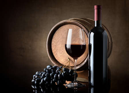 Bottle of red wine, grapes and wooden barrel photo