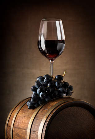 wine background: Wine goblet with wooden barrel and grape