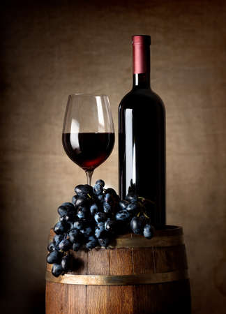 Fles rode wijn, glas wijn, druiven en houten vat