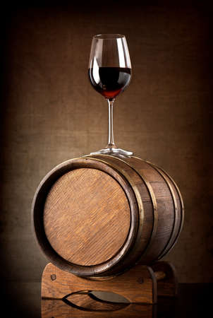 wine background: Red wine and glass with wooden barrel Stock Photo