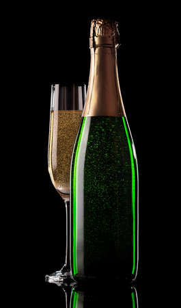 Glas en fles champagne op een zwarte achtergrond Stockfoto