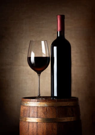 wine barrel: Wine standing on a barrel on a background of a canvas Stock Photo