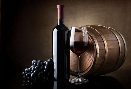 Bottle of red wine, grapes and wooden barrel Imagens