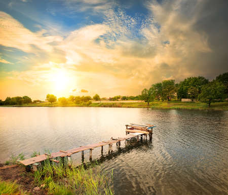 Wooden dock, pier, on a lake in the evening photo