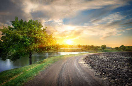 Sunset over the country road the river photo