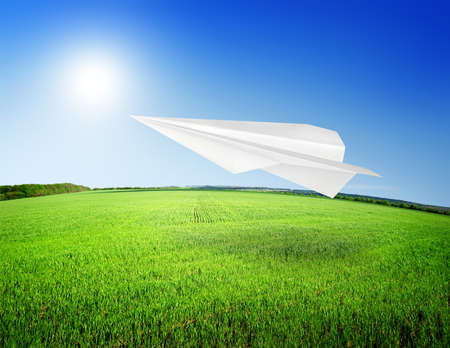 Field of grass and paper airplane. Perfect blue sky photo