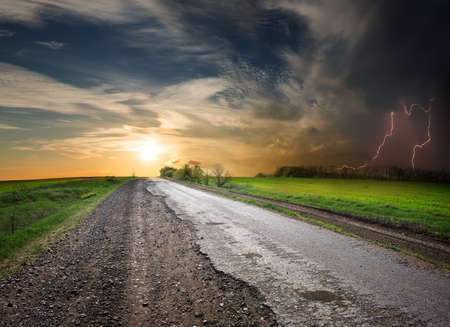 field stripped: Asphalted road at sunset and stormy sky Stock Photo