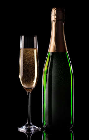 Glass and bottle of champagne on black background photo