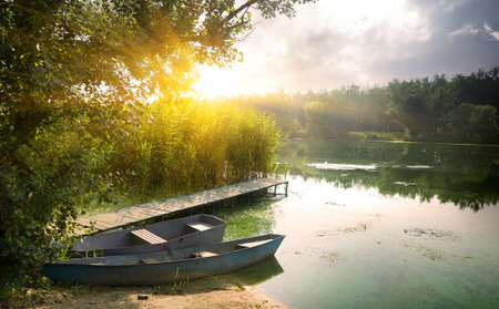 Boats on river at beautiful summer sunrise photo