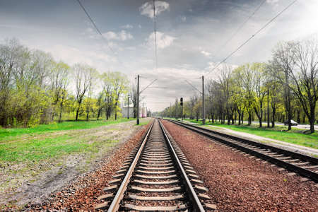 Gray cloudy sky over railroad in spring photo