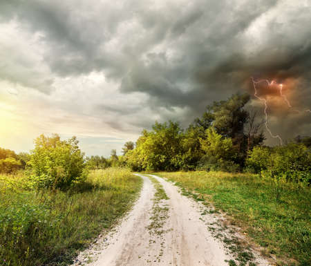 Country road through the forest and lightning photo