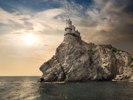 golondrinas: Rocas en el mar bajo el cielo nublado