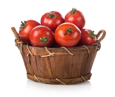 basket: Red tomatoes in a basket isolated on white Stock Photo