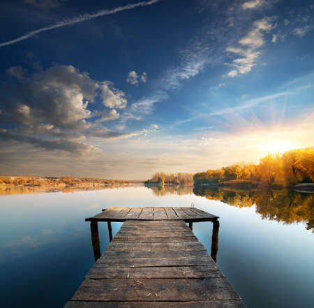 Pier on a calm river in the autumn photo