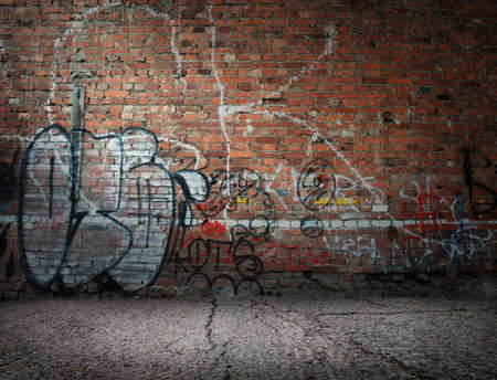 Graffiti on the old wall of red brick