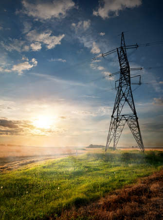 conduction: Electric pole and autumn field at sunrise Stock Photo