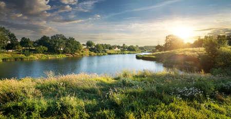 Blauwe rivier onder wolken bij de zonsondergang