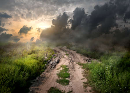 dark clouds: Fog and dirt over country road at sunset