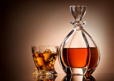 Decanter and glass of golden whiskey on brown background