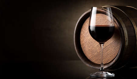 glass table: Wineglass of red wine and barrel on brown background Stock Photo