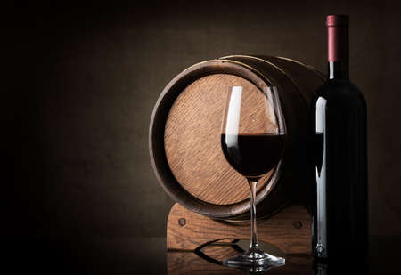 glass table: Red wine near wooden barrel on a brown background Stock Photo