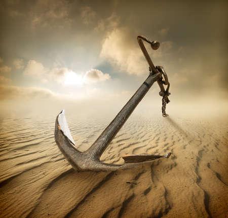 Anker in der Wüste und bewölktem Himmel Standard-Bild