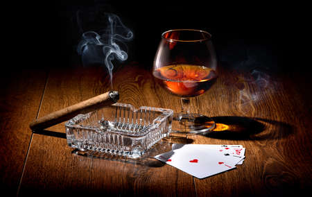 Playing cards near wineglass of whiskey and cigar photo