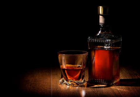 Botella y vaso de whisky en una mesa de madera