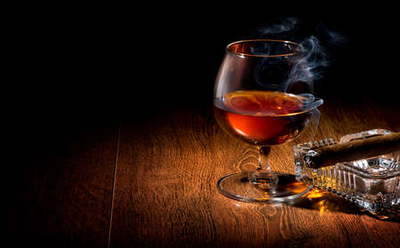 cigarro: Coñac y cigarro en el cenicero en una mesa de madera