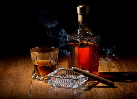 Brandy and cigar on ashtray on a wooden table