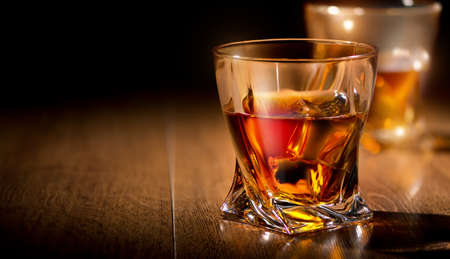 Glasses of whiskey on a wooden table photo