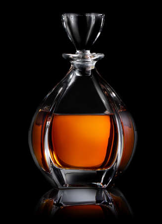 Decanter of cognac on a black background Imagens