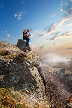 Tourist on a high rock at sunrise photo