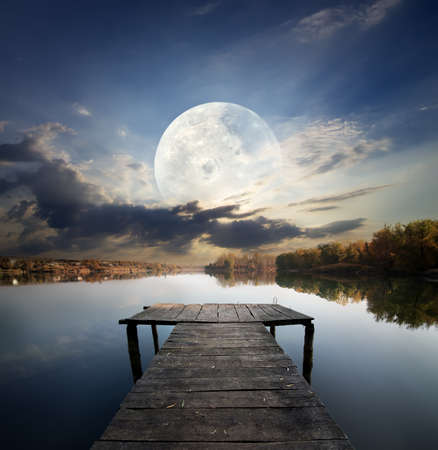 fool moon: Fishing pier on a river under fool moon. Elements of this image furnished by NASA
