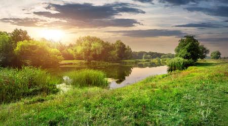 Zonnige zonsondergang over kalme rivier in het bos
