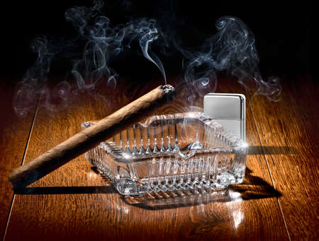 ashtray: Cigar on ashtray and silver lighter on a wooden table