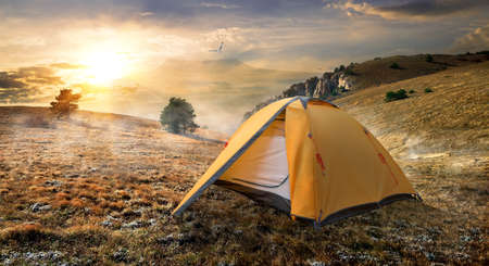 Tourist tent in autumn mountains at sunrise