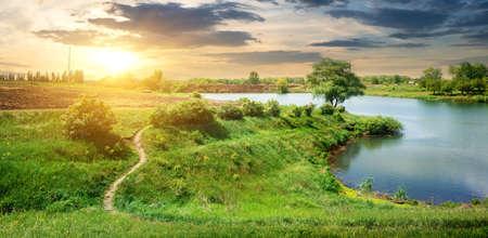 green river: Footpath near calm river in spring at sunrise